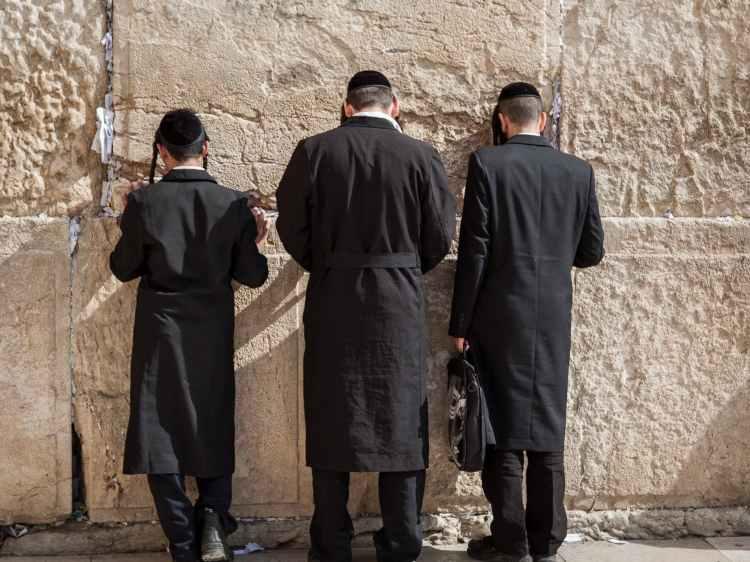 anonymous religious hasidim jews during pray near western wall